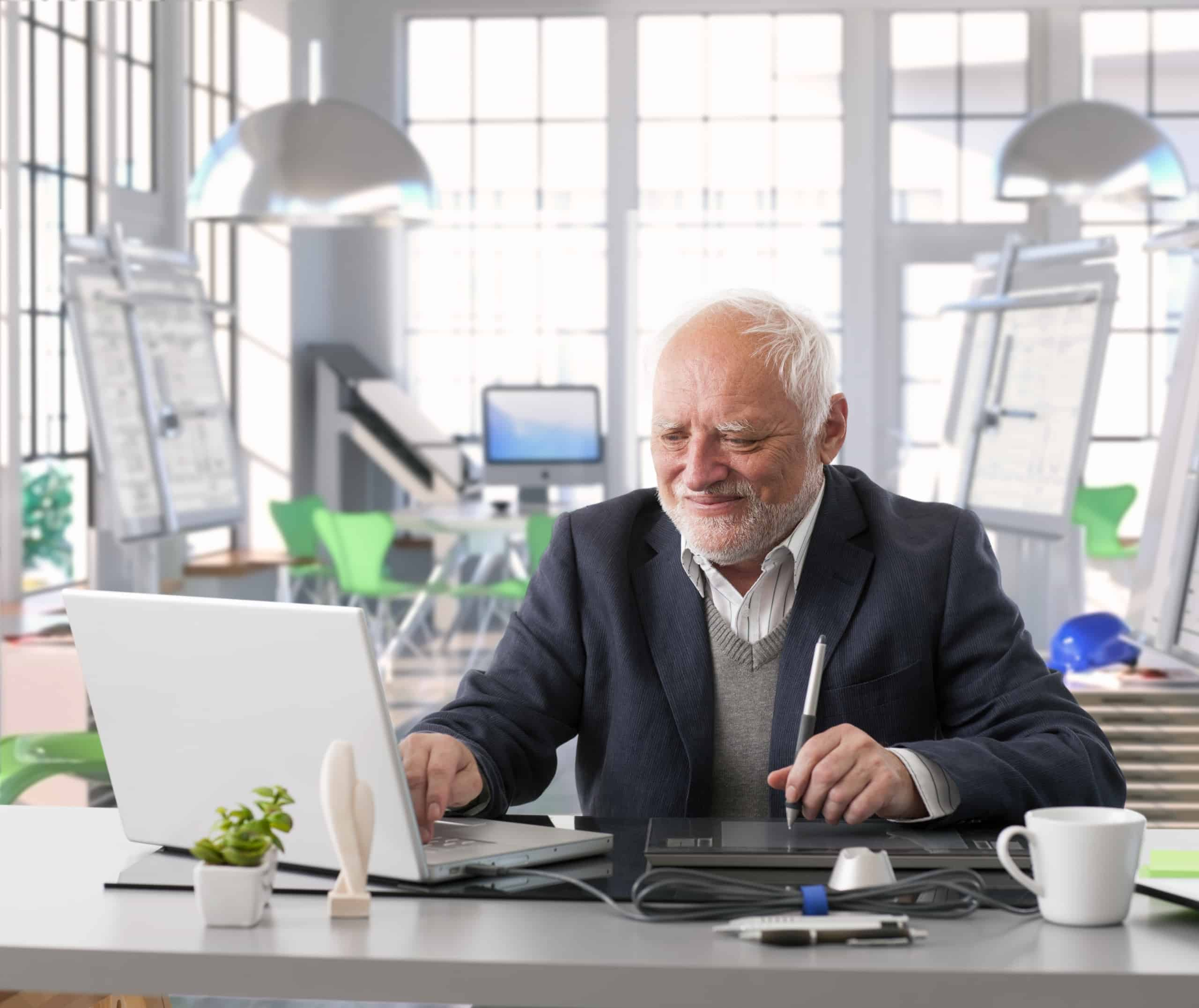 Senior employee working on laptop in office