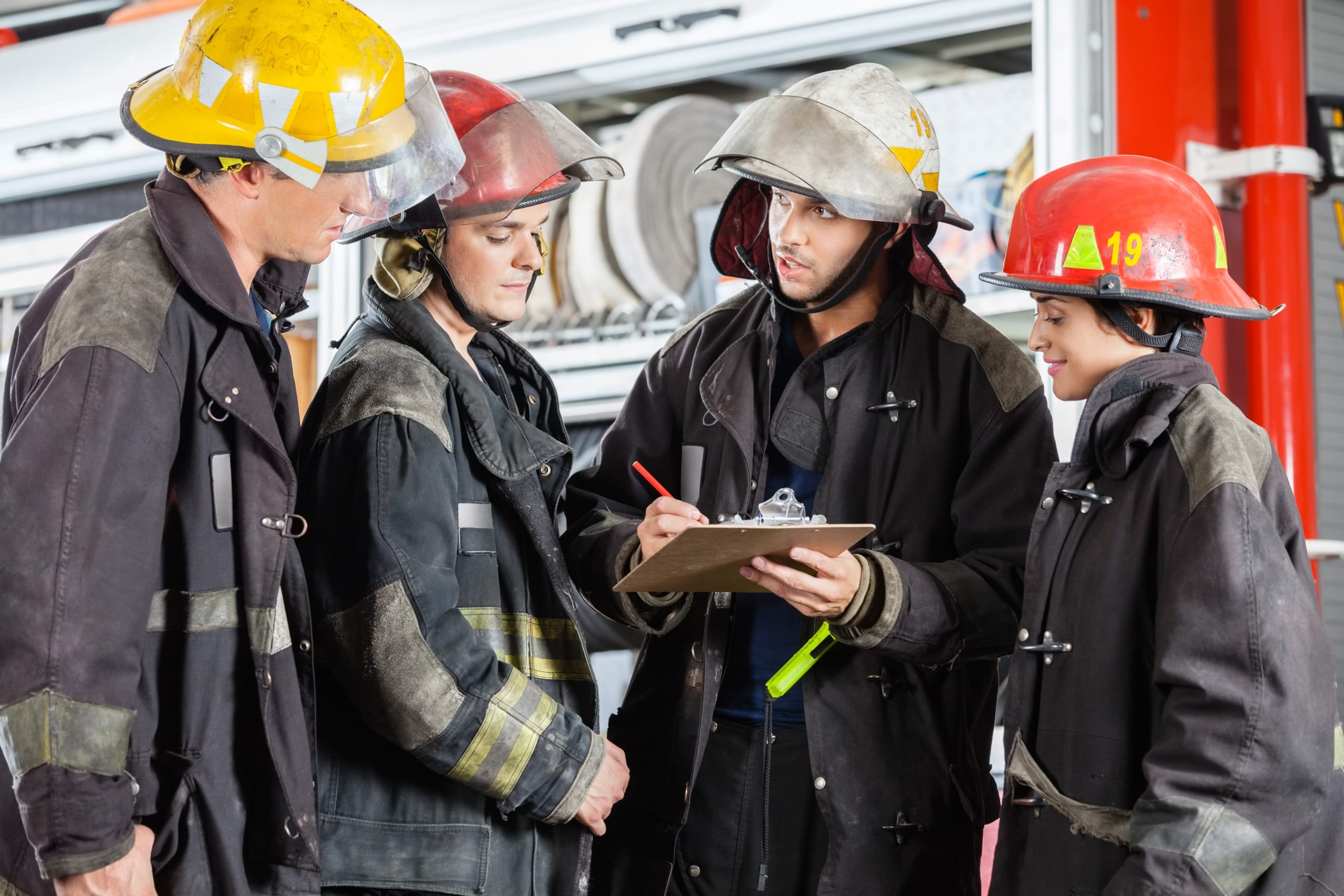 Team Of Firefighters Discussing Over Clipboard
