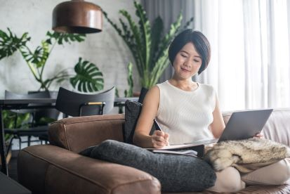 Happy Woman Working From Home Using Laptop and Pen